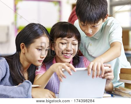 three happy asian elementary school students looking at tablet computer smiling in classroom.