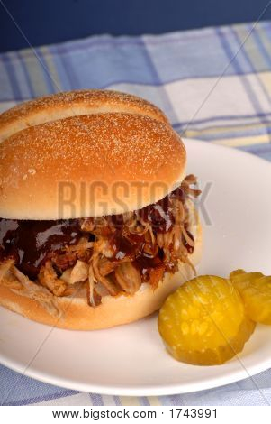 Pulled Pork Sandwich With Pickles On A White Plate