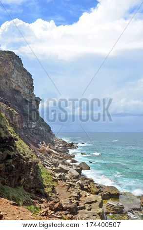 Rugged coastal cliffs and rocky shore at Garie beach on the New South Wales coast, Royal National Park, Australia