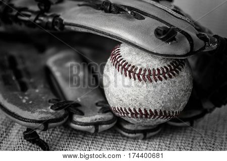 horizontal close up black and white vintage image of an old worn baseball  with red thread and catchers mitt.