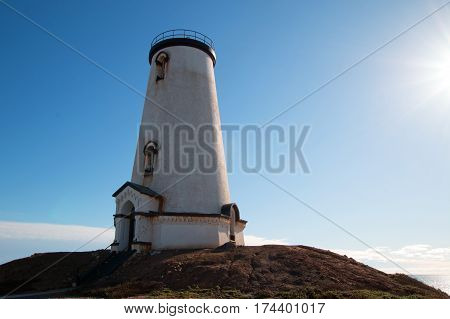 Lighthouse at Piedras Blancas point glowing in the afternoon sunlight on the Central California Coast north of San Simeon California USA