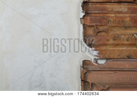 Detail of white grungy wall texture with roof tiles, stucco walls and vintage red tiles background
