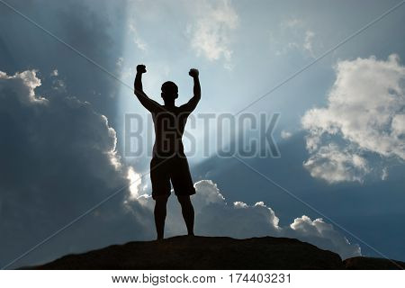 Positive male holding hand up and expressing gladness while standing on stone.