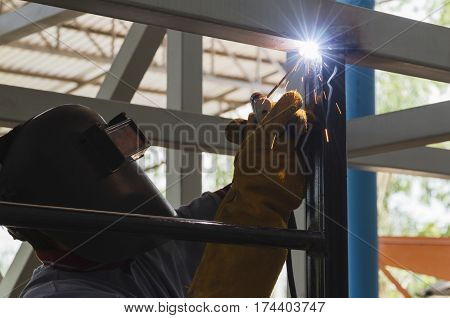 Welder in position over head action, were welding steel structural by arc welding - Shield metal arc, At steel structure manufacturing industry.