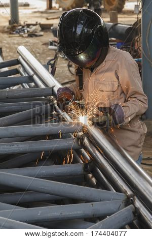 Worker with safety equipment and protective mask welding steel structure in construction factory - Use the wrong kind equipment.