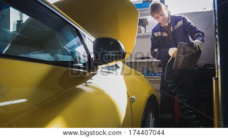 Car mechanic blows air filter of automobile in service, close up