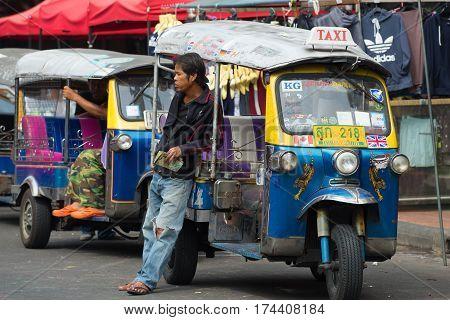 BANGKOK, THAILAND - JANUARY 06, 2017: The driver of the old tuk-tuk waiting for passengers