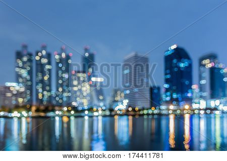 Twilight city office building blurred light with water reflection abstract background
