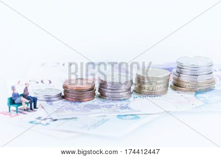 Miniature man and woman saving for retirement