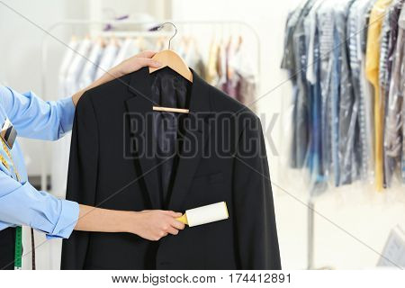 Woman with adhesive roller cleaning clothes in dry-cleaning salon