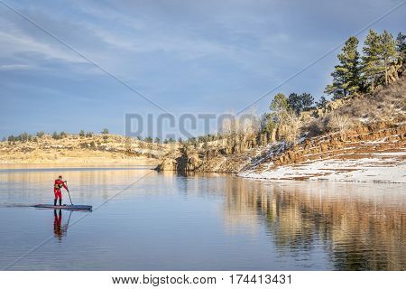 male paddler in a red drysuit  enjoying stand up paddling on a mountain lake in Colorado - Horsetooth Reservoir near Fort Collins