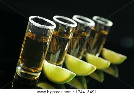 Row of golden tequila shots with juicy lime wedges and salt on black background