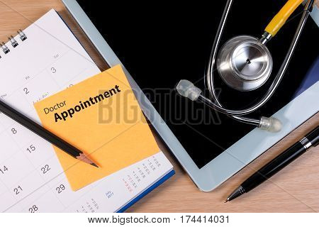 Close Up Of Doctor Appointment, Stethoscope Book And Pen On Calendar. Booking Reminder Plan For Doct