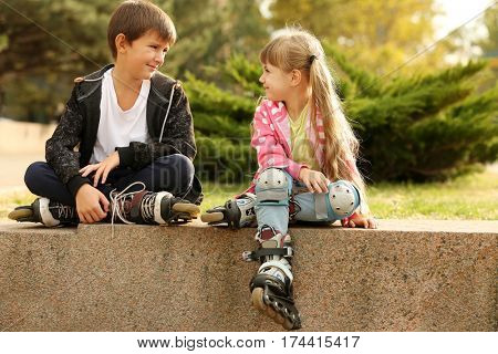 Cheerful friends in roller skates sitting on border in park