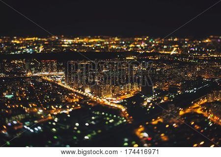True tilt shift shooting of residential district of night metropolis from very high above: multiple residential houses and orange lights from windows strong bokeh in background and foreground