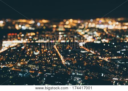 True tilt shift shooting of night metropolis from very high above: multiple warm colorful lights strong bokeh in background street of residential district in focus in foreground