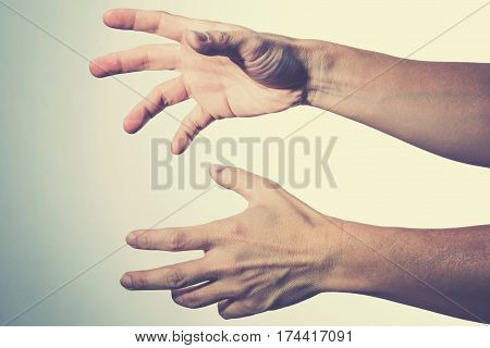 two male hands reaching out in harsh light and contrasty cross process color style showing unconfortable and desperate feels