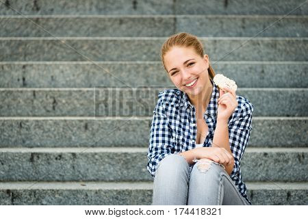 Healthy lifestyle  - teenager eating puffed bread outdoor sitting on stairs