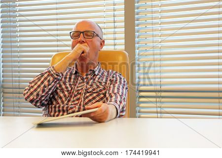 weariness - tired,yawning middle age man in eyeglasses,with tablet