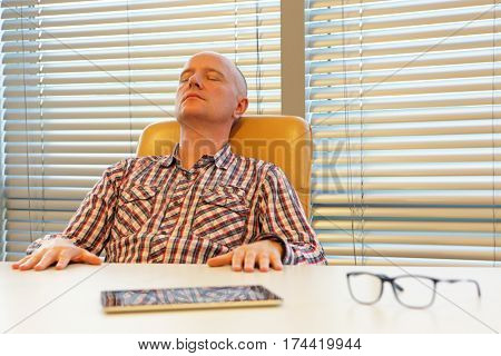 middle age balding man relaxing in office - short break for regeneration