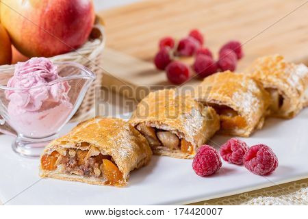 Fresh berry dessert on grey background. Puff pastry with fruit on a brown background. Mille-feuille of puff pastry with raspberries on a wooden Board.