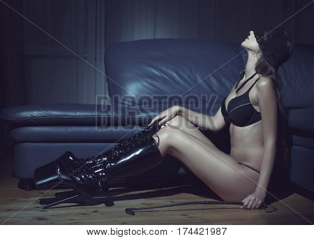 Sensual woman in underwear and lace eye cover and latex boots sit on floor in dark desire. Book cover template
