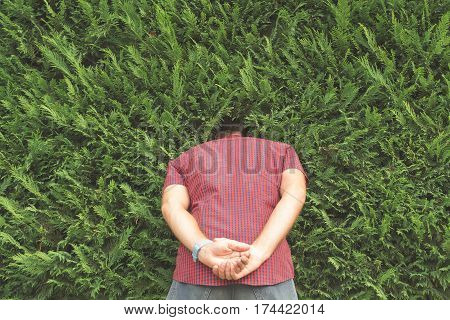 Guy hiding his head in the bushes.