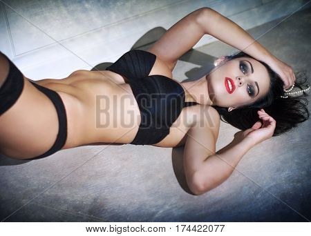 Sexy brunette woman lying on floor at night book cover template