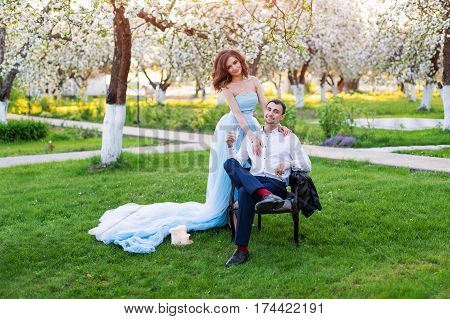 Groom and bride together, wedding couple. Young couple embracing in blooming spring garden. Love and romantic theme