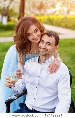 Groom and bride together, wedding couple. Young couple embracing, drinking champagne in blooming spring garden. Love and romantic theme