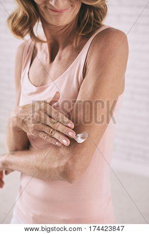 Slim senior woman applying lotion to her body