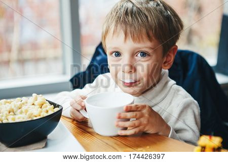 Portrait of cute adorable Caucasian child kid boy drinking milk from white cup eating breakfast lunch early morning everyday lifestyle candid moments