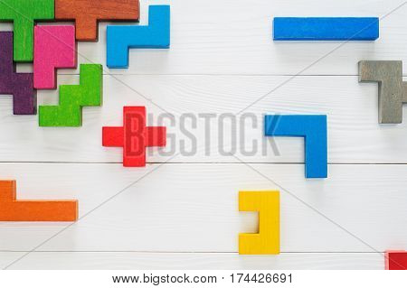 Concept of creative logical thinking. Different colorful shapes wooden blocks on white wooden background flat lay copy space. Geometric shapes in different colors top view. Abstract Background.