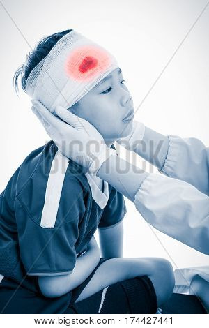 Athlete asian boy with trauma of the head. Doctor makes a bandage on head patient. Child unhappy on white background. Color increase blue skin and red spot indicating location of pain. Studio shot