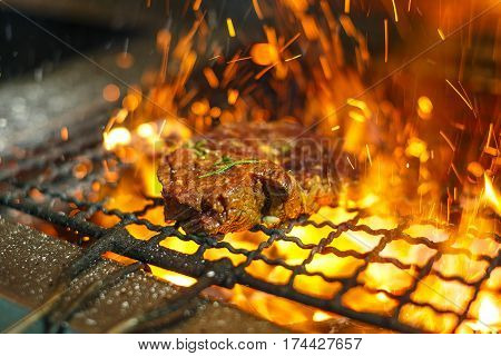 Beef steaks on the grill with flames. Grilled meat in barbecue with flames and coals. Grill meat. Empty Hot Charcoal Barbecue Grill With Bright Flame On The Black Background.