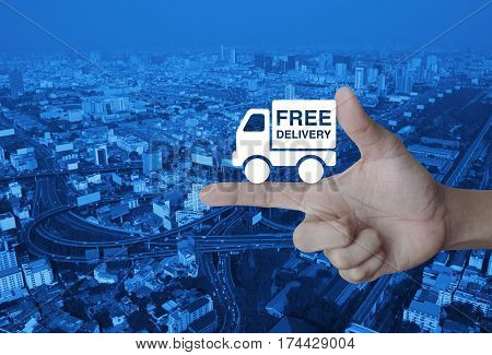 Free delivery truck icon on finger over modern city tower street and expressway Transportation business concept