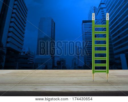 Green pencil ladder on wooden table over modern office city tower Business success concept