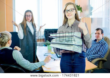 Girl in a gray tank top and sunglasses holding a large stack of briefs. People heavily loaded with work. Facial emotions worker fatigue