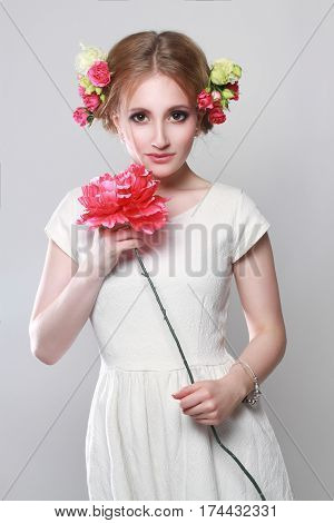 Charming Blonde with flowers in her hair and in her hands. Bright spring model with natural make-up on her face. Girl on a light gray background holds a flower in his hand. In anticipation of spring