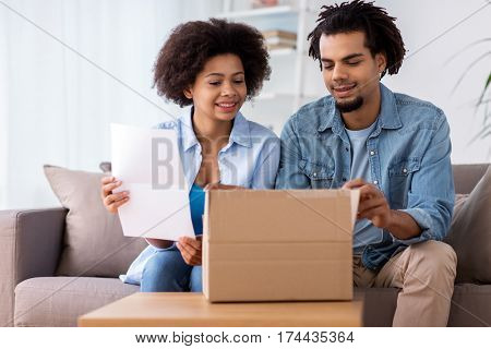 people, delivery and consumerism concept - happy couple with parcel box and paper form home