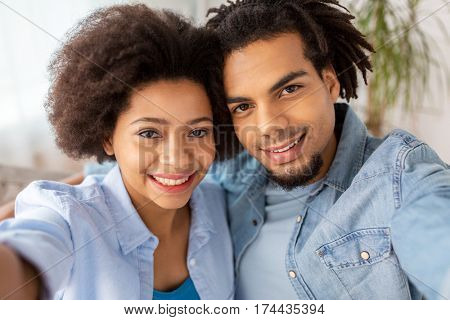family, technology and people concept - happy couple taking selfie at home