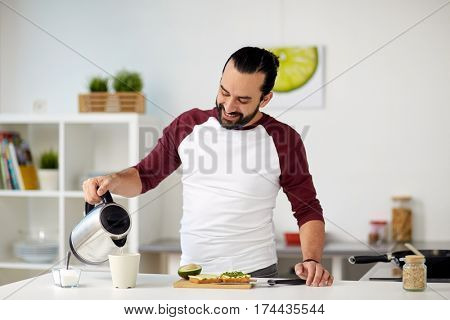 vegetarian food, healthy eating, people and diet concept - man with kettle making tea and having vegetable sandwiches for breakfast at home kitchen