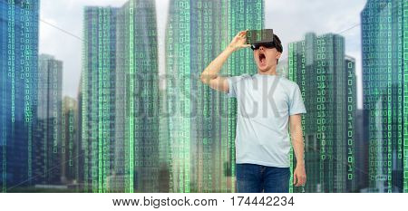 modern technology, entertainment, cyberspace and people concept - amazed young man with virtual reality headset or 3d glasses over city skyscrapers and binary code background