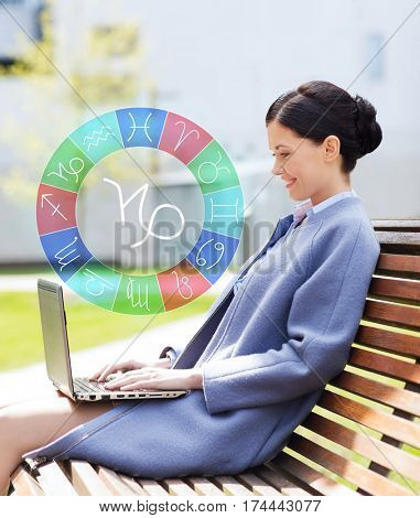 astrology, horoscope, technology and people concept - young smiling woman with laptop and capricorn zodiac sign computer sitting on bench in city