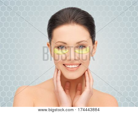 beauty, cosmetology, hydration, people and rejuvenation concept - beautiful young woman face with hydrogel under-eye patches over gray background