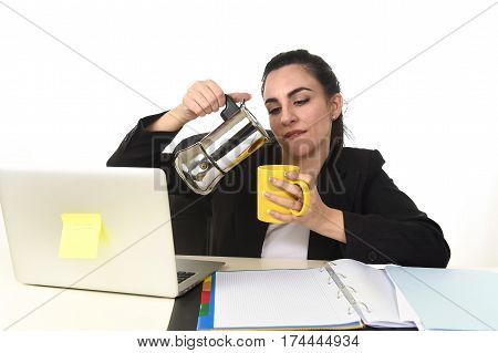 young attractive business woman at laptop computer desk pouring coffee on cup directly from coffee pot excited and anxious in caffeine addiction concept isolated on white background