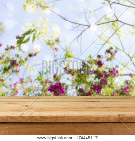 Empty wooden deck table over blooming flowers background for product montage display