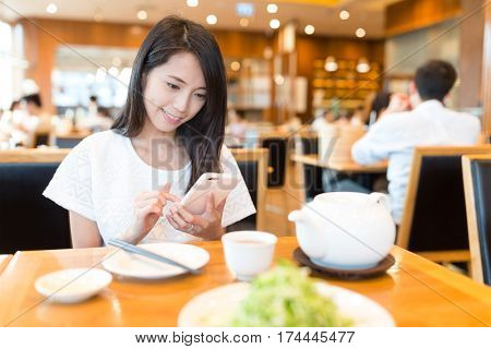 Woman use of mobile phone at chinese restaurant