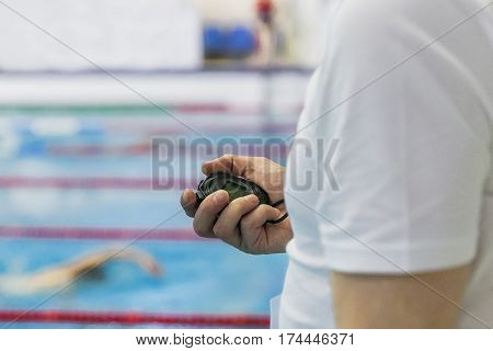 referee timekeeper with stopwatch in hand in swimming competition