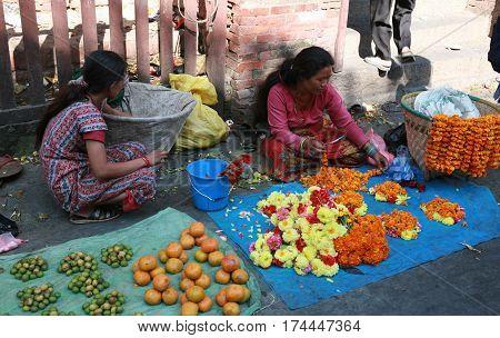 KATHMANDU, NEPAL. 23 September 2008: Young woman near the Temple sell garlands of flowers for pilgrims-Hindu. Patan, Durbar Square, Nepal
